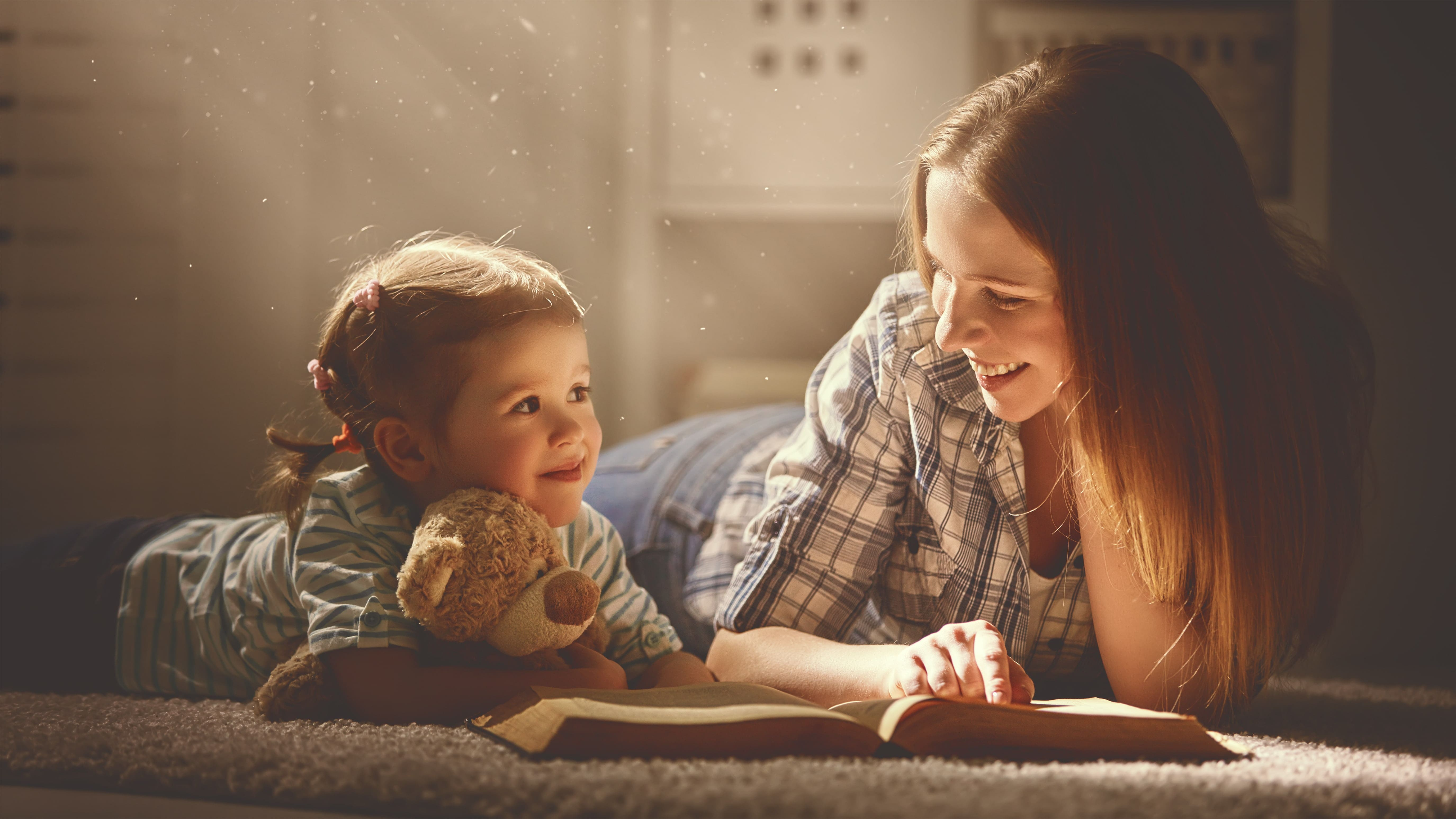 parent with custody reading a book together with her child